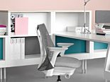 bright, clean photo of white and grey Herman Miller Sayl chair beside all white desk space