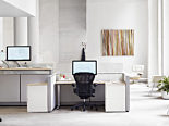 brightly lit office space. segmented desk space featuring the Herman Miller Aeron office chair in black.