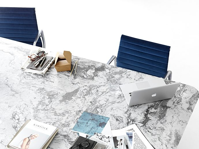 white and grey marble table with work materials such as notebooks on it.