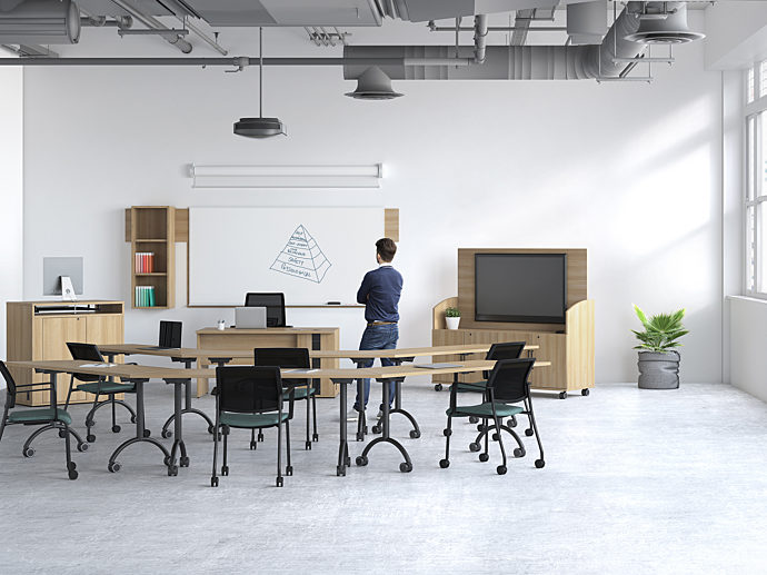 Person standing in classroom with mobile furniture and mobile technology