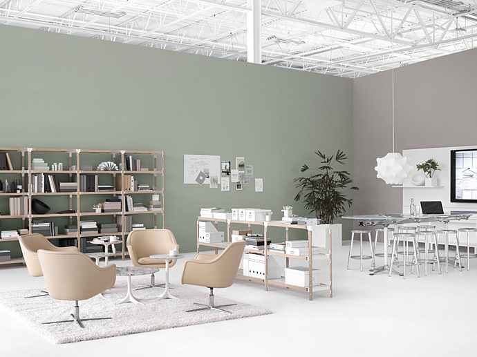 open plan office space. Left hand side with simple tan lounge chairs. Right side with a high top conference table and metal stools, tv on far right wall.