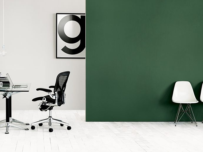 Left hand side of room with white walls with a glass desk and black office chair. The right is two white Eames Molded Plastic chair against green wall.