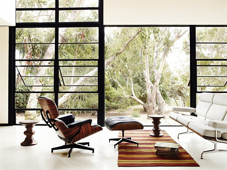 Classic Eames Lounge and ottoman paired in a modern livingroom with  walnut stools an Eames sofa with a large picture window in the background.